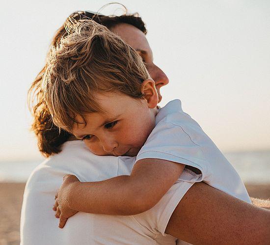 Junge in den Armen seiner Mutter