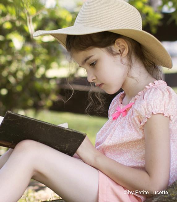 Mädchen lesend mit Liberty-Bluse und Sommerhut